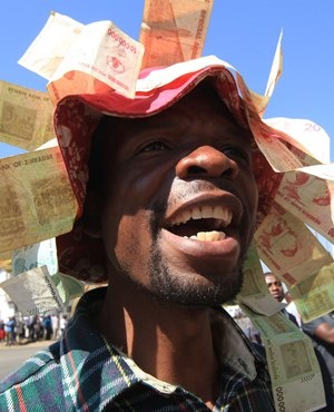 A man wears a hat with old Zimbabwean dollar notes during  demonstrations in Harare, Wednesday, August, 3 2016. Zimbabwean police have fired teargas  and water cannons to  break up anti government protests in the  capital Harare.Police beat up several journalists covering the  protests Wednesday, smashing  a video camera and attacking a journalists car, breaking windows and taking a laptop(AP Photo/Tsvangirayi Mukwazhi)