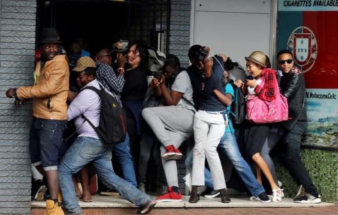 Students demanding free education react as they are fired at by riot police officers during a protest outside the University of the Witwatersrand at Braamfontein, in Johannesburg, South Africa, October 10,2016. REUTERS/Siphiwe Sibeko