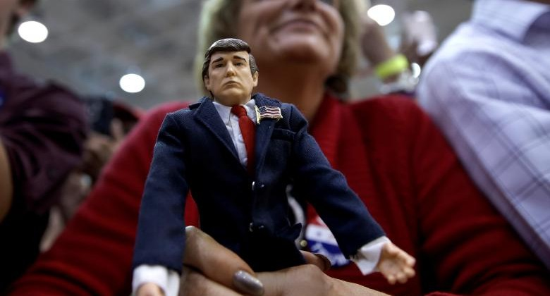 A supporter of Donald Trump holds a Trump doll as she listens to him speak at a campaign rally in Ambridge, Pennsylvania. REUTERS/Mike Segar